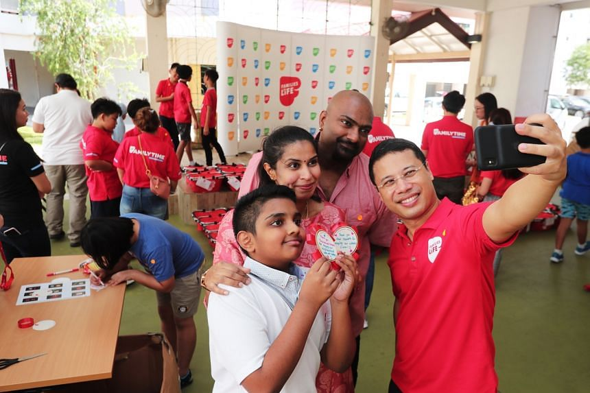 Minister for Social and Family Development Desmond Lee (right) taking a wefie with Mr Gunalan Shiva, 46, Mrs Jacintha Francis, 38, and Caelan Gunalan, 11, family volunteers for Share-the-Care movement.