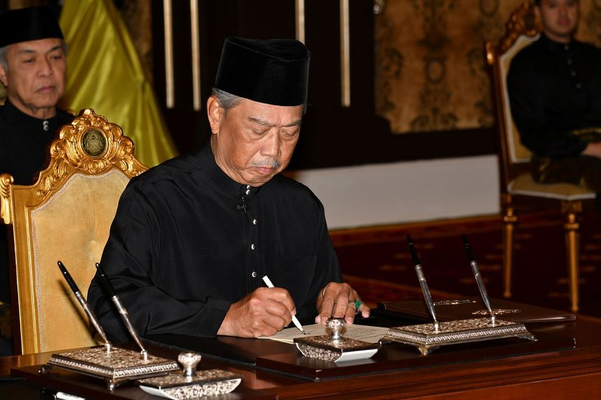 Muhyiddin Yassin signs a document during swearing-in ceremony as Malaysia's prime minister in Kuala Lumpur, Malaysia, on March 1, 2020.