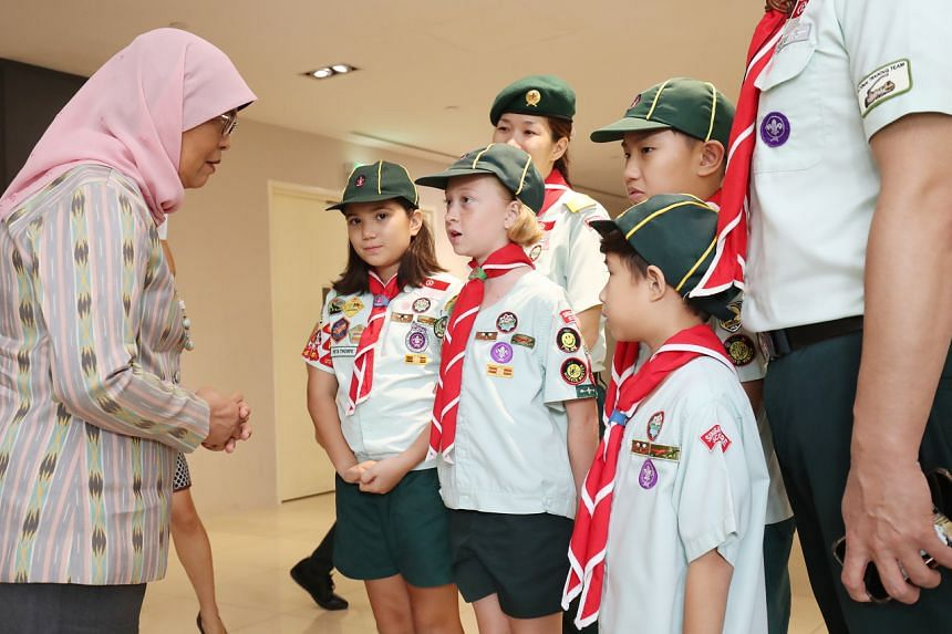 President Halimah Yacob (left) speaks to members of The Singapore Scout Association. The Scouts and Girl Guides here are writing thank you letters to healthcare workers, to show their appreciation for the workers who are battling the Covid-19 outbrea