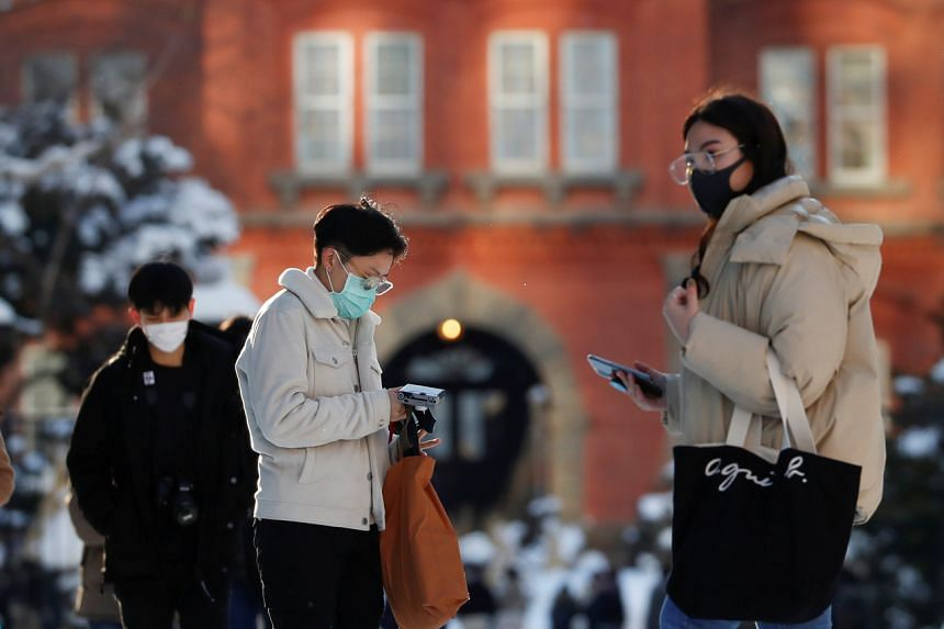 People wearing masks are seen in front of the former Hokkaido Government Office building in Sapporo, Hokkaido, on Feb 26, 2020.