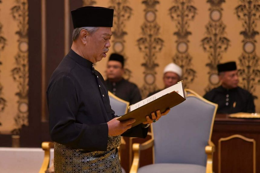 Malaysia's incoming Prime Minister Muhyiddin Yassin reading the oath during his swearing-in ceremony as the country's new leader at the National Palace in Kuala Lumpur.