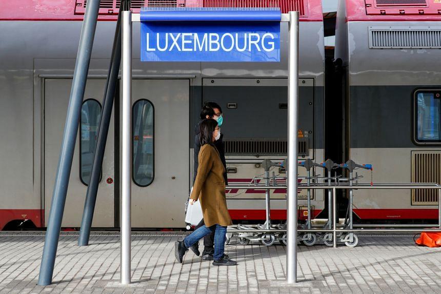 Tourists wearing masks walk on a platform at Luxembourg railway station, on Feb 29, 2020.