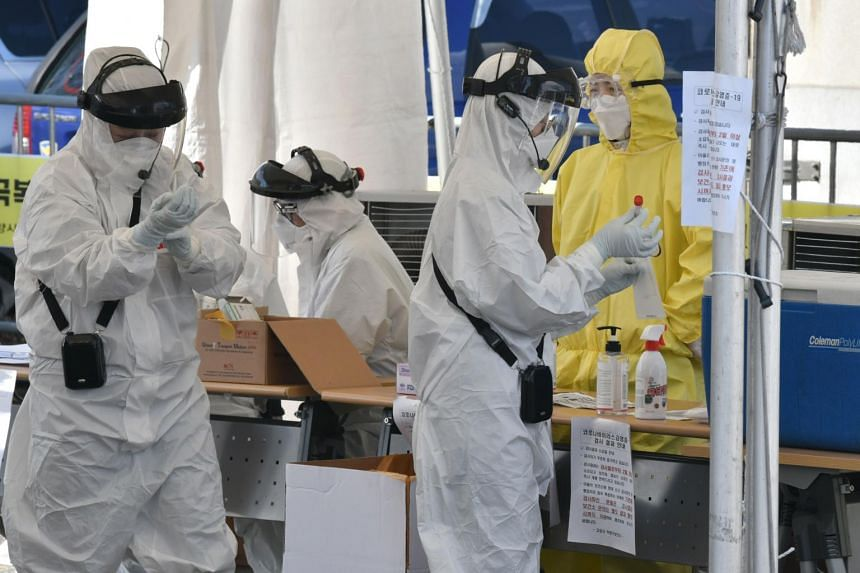 """Medical members take samples from a driver with suspected symptoms of the coronavirus, at a """"drive-through"""" virus test facility in Goyang, north of Seoul, on Feb 29, 2020."""