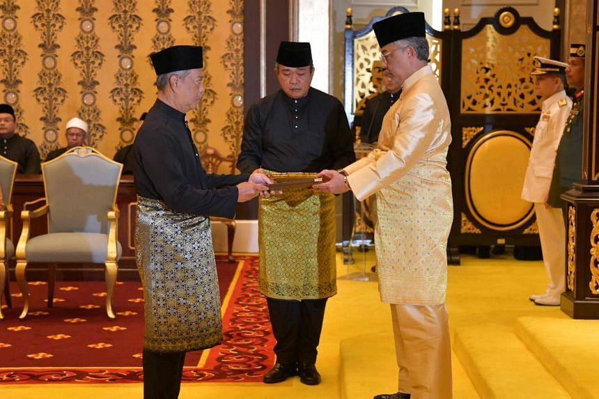 Malaysia's incoming Prime Minister Muhyiddin Yassin (left) receiving documents from King Sultan Abdullah Sultan Ahmad Shah (right) before taking the oath as the country's new leader.