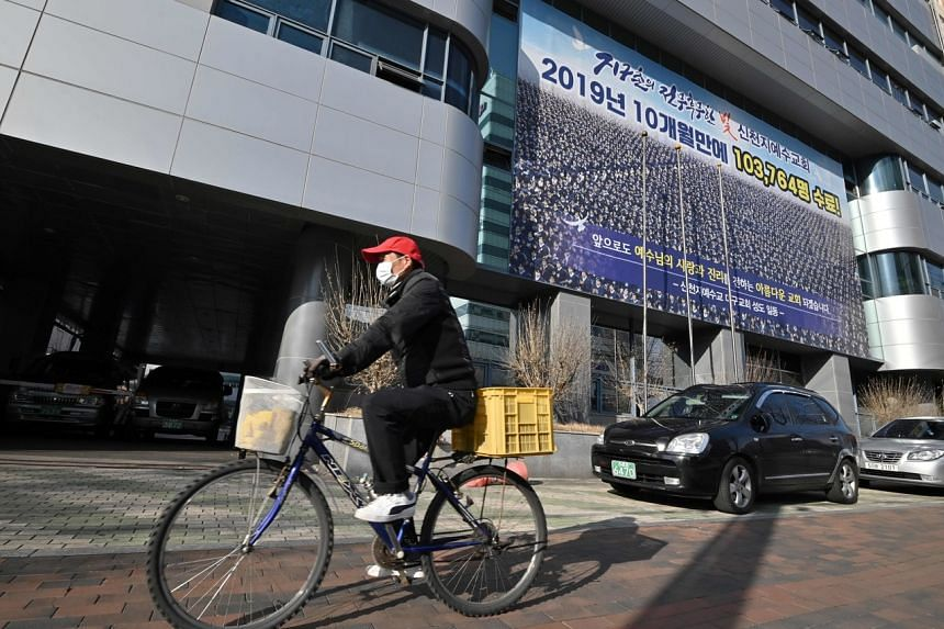 A man wearing a face mask rides a bicycle in front of the Daegu branch of the Shincheonji Church of Jesus, on Feb 27, 2020.