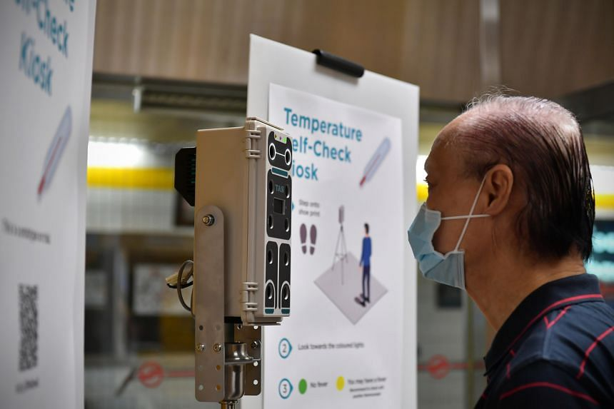 Lim Shaw Leng, 78, getting his temperature checked at a kiosk at Toa Payoh MRT Station on March 1, 2020.