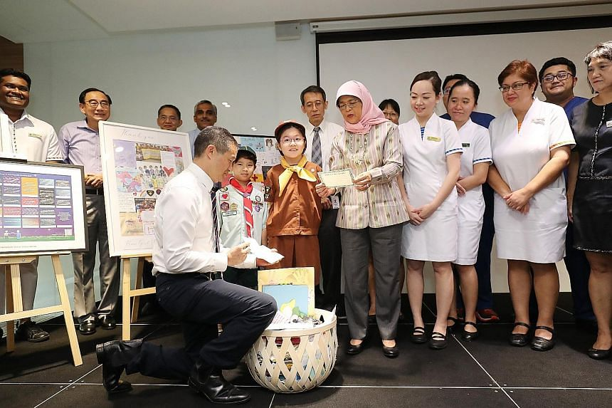 President Halimah Yacob and Professor Kenneth Kwek, SingHealth's deputy group chief executive, looking at some of the cards written by Scouts and Guides here. With them were Singapore General Hospital senior management and staff, who received the let