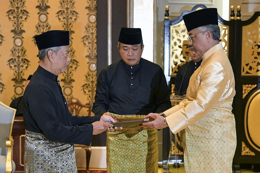 Malaysia's incoming Prime Minister Muhyiddin Yassin (far left) receiving documents from the King, Sultan Abdullah Ri'ayatuddin, before taking the oath as the country's new leader at the National Palace in Kuala Lumpur yesterday.