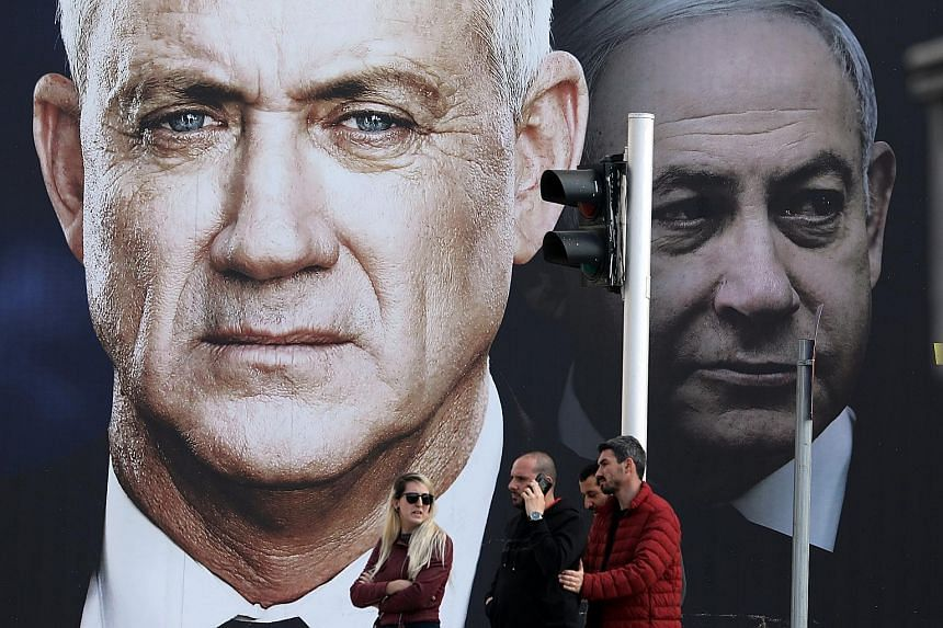 The Blue and White alliance's election banner, which depicts its leader Benny Gantz and Israeli Prime Minister Benjamin Netanyahu, in Tel Aviv last week. Both the Blue and White and Mr Netanyahu's Likud have been projected to fall short of forming a