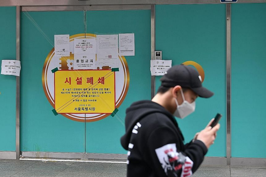 A man walking past a branch of the Shincheonji Church of Jesus, the Temple of the Tabernacle of the Testimony, in Seoul. The church has been temporarily closed by the South Korean government to help prevent the spread of the coronavirus after a large