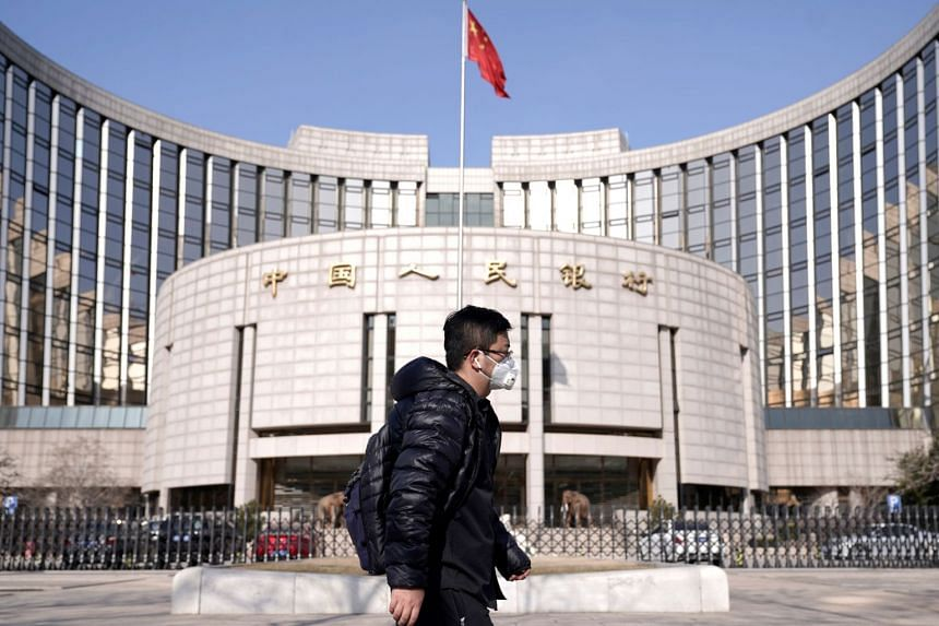 A man wearing a mask walks past the headquarters of the People's Bank of China, the central bank, in Beijing, China, on Feb 3, 2020.