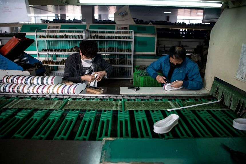 Workers applying glue on soles at the Zhejiang Xuda Shoes factory in Wenzhou.