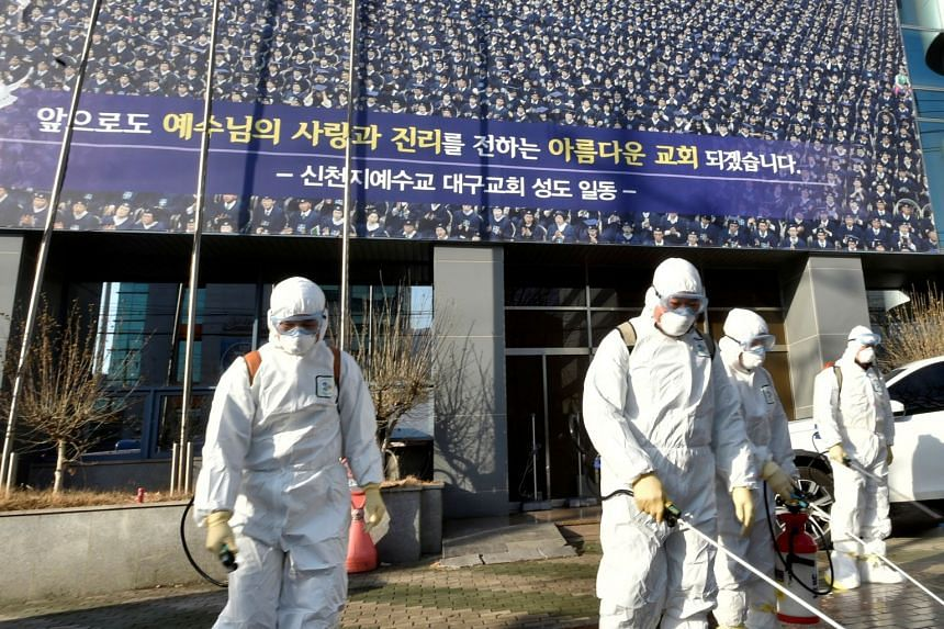Workers sanitise a street in front of a branch of the Shincheonji Church of Jesus in Daegu, South Korea, on Feb 19, 2020.
