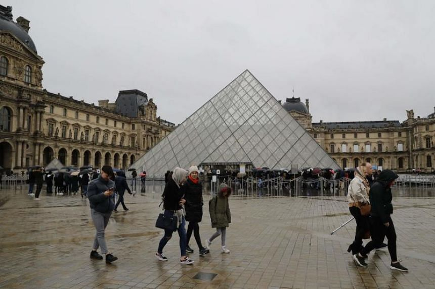 People wait in front of the Louvre entrance under a drizzle in Paris, on March 1, 2020.