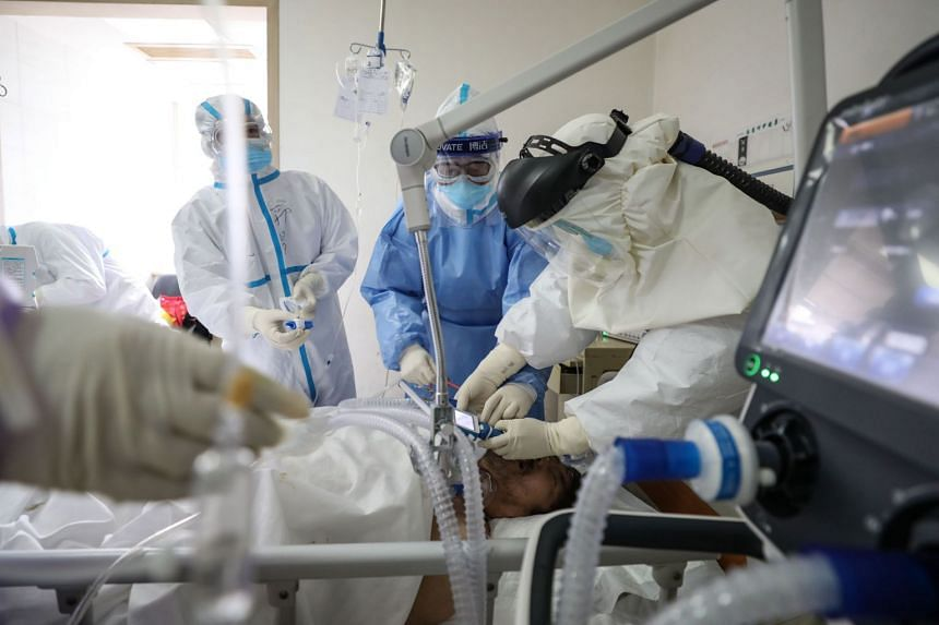 Medical staff treat a patient infected by the coronavirus at the Red Cross hospital in Wuhan on March 1, 2020.
