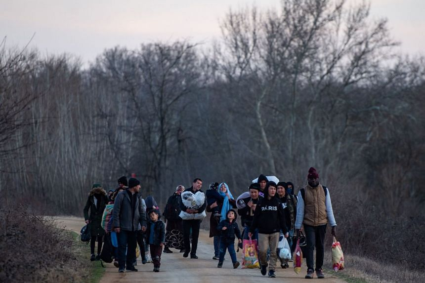 Migrants walk on a road toward the Meritsa river, near Edirne in northwestern Turkey, to take a boat to attempt to enter Greece on March 1, 2020.