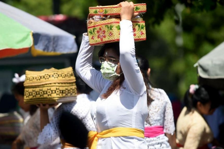 A mask-clad Balinese woman during the Galungan holiday at Jagatnata temple in Denpasar, Indonesia, on Feb 19, 2020.
