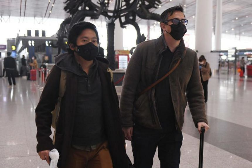 Wall Street Journal staff Josh Chin (right) and Philip Wen walk through Beijing Capital Airport before their departure on Feb 24, 2020.
