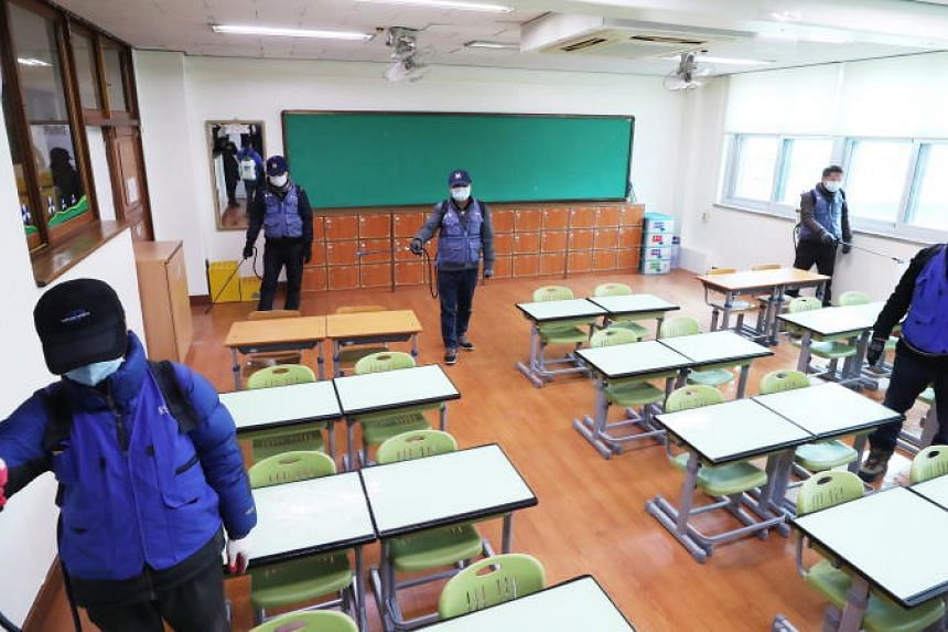 Quarantine officials disinfect a classroom at an elementary school in Suwon, South Korea, on Feb 19, 2020.