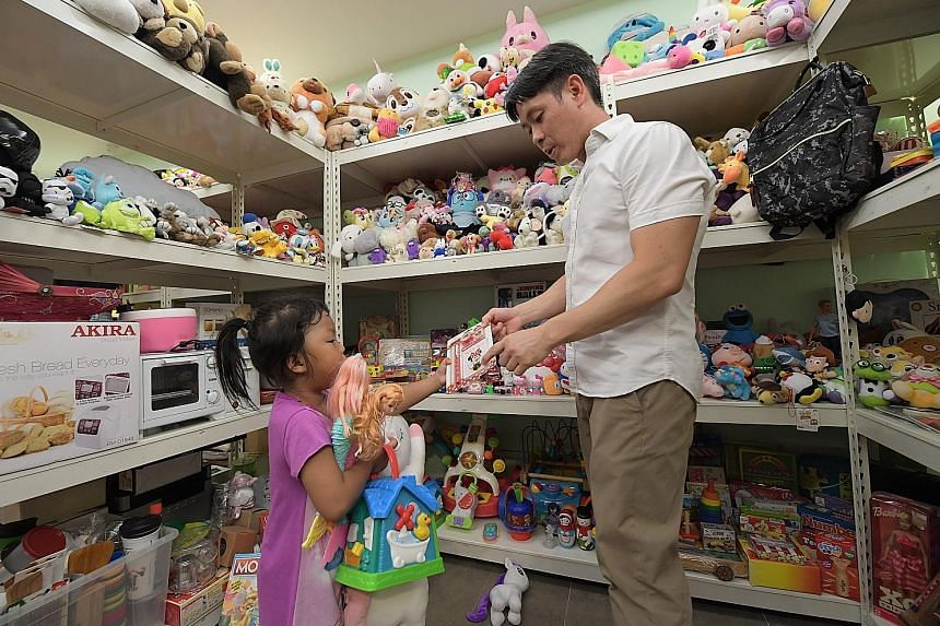 Nee Soon GRC MP Louis Ng offering a child a toy from Project Hope's room full of donated items at the Residents' Committee at Block 227 Yishun Street 21 on Feb 24, when several low-income households were invited to pick a fixed number of items. Mr Ng