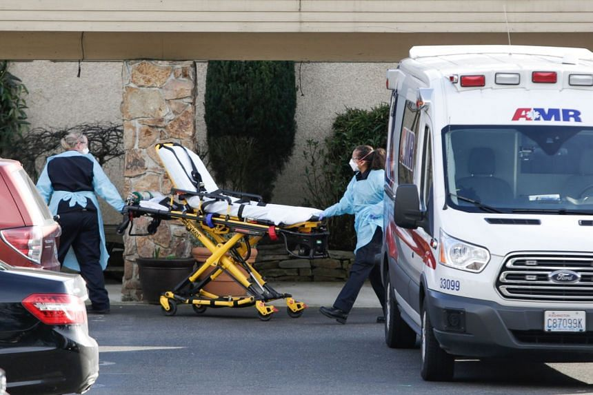 A stretcher is moved from an ambulance to the Life Care Center of Kirkland in Washington on Feb 29, 2020.