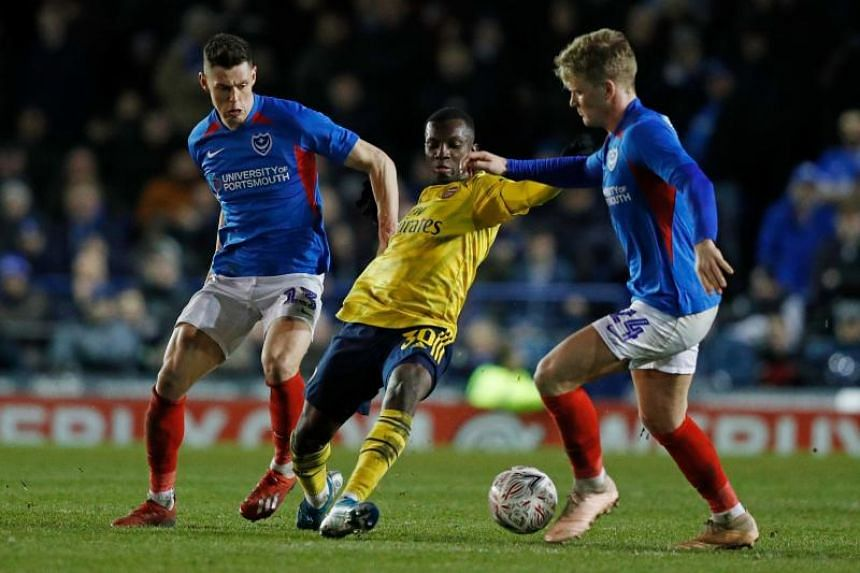 Arsenal striker Eddie Nketiah (centre) takes on Portsmouth's players James Bolton (left) and Cameron McGeehan (right) during the English FA Cup fifth round football match at Fratton Park stadium in Portsmouth, southern England, on March 2, 2020.