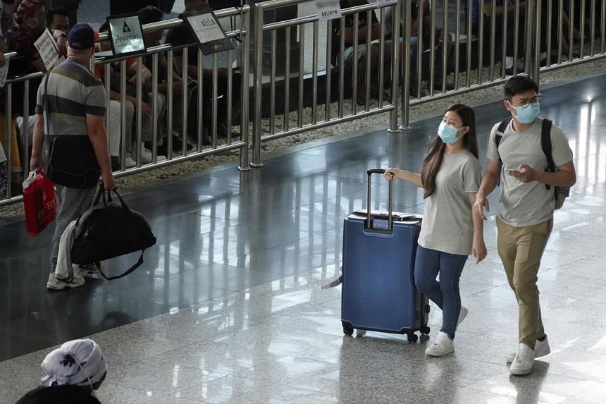 Passengers wear protective masks upon arrival at Ngurah Rai International Airport in Bali, Indonesia, on March 2, 2020.