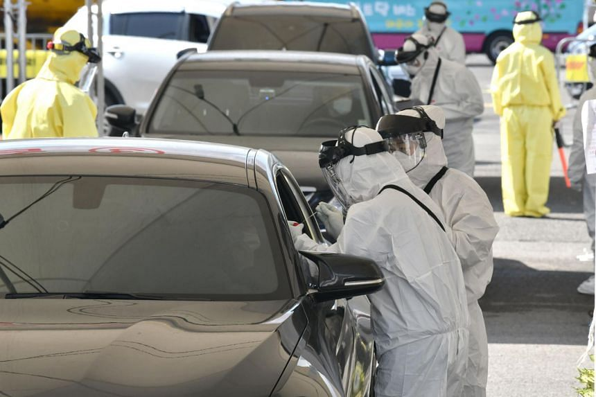 """Medical staff wearing protective gear take samples from a driver with suspected symptoms of the coronavirus, at a """"drive-through"""" virus test facility in Goyang, north of Seoul, on Feb 29, 2020."""