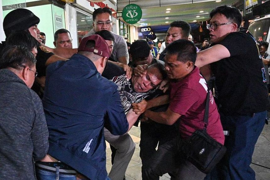 Police subduing the gunman outside the mall at a commercial hub east of Manila yesterday. He had shot and injured a security worker and held around 60 people hostage in the mall for nearly 10 hours. After the hostages were let out, the gunman himself