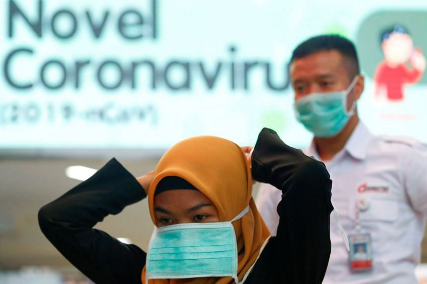 A woman puts on a protective mask at Sudirman Station in Jakarta, on Feb 4, 2020.