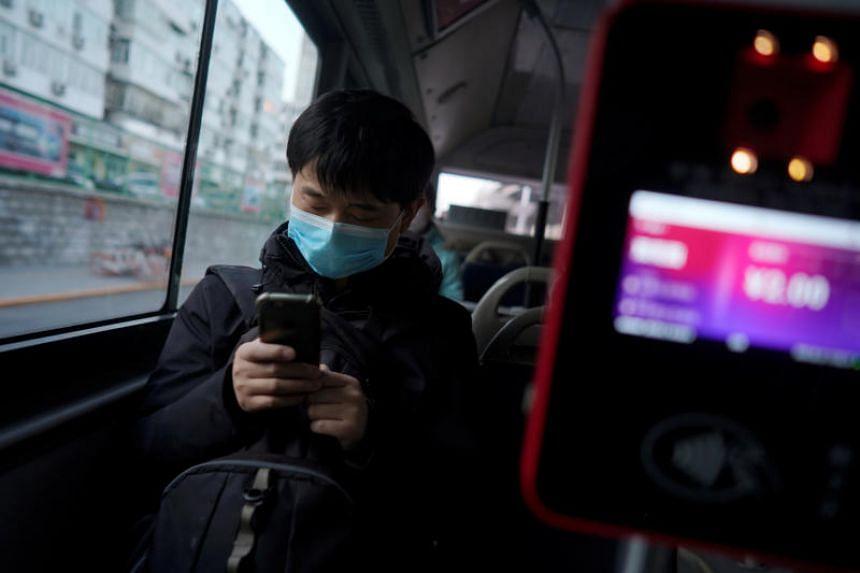 A bus passenger checks his mobile phone in Beijing on Feb 21, 2020.