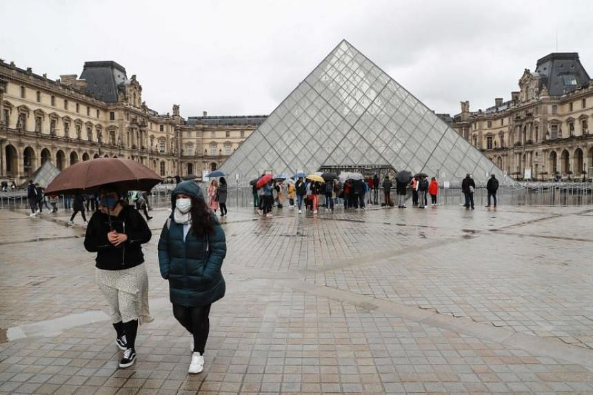 People in masks are seen outside the Louvre museum in Paris on March 2, 2020.