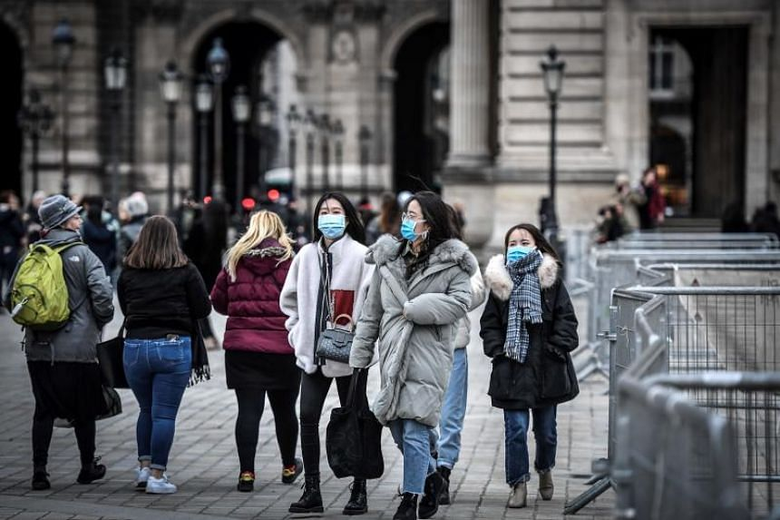 Tourists wearing a protective face mask walk at the Pyramide du louvre area in Paris on Feb 28, 2020.
