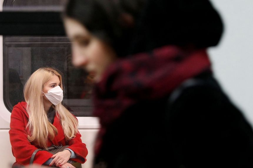 A woman wearing a protective face mask sits inside a train at a subway station in Milan, Italy, March 3, 2020.