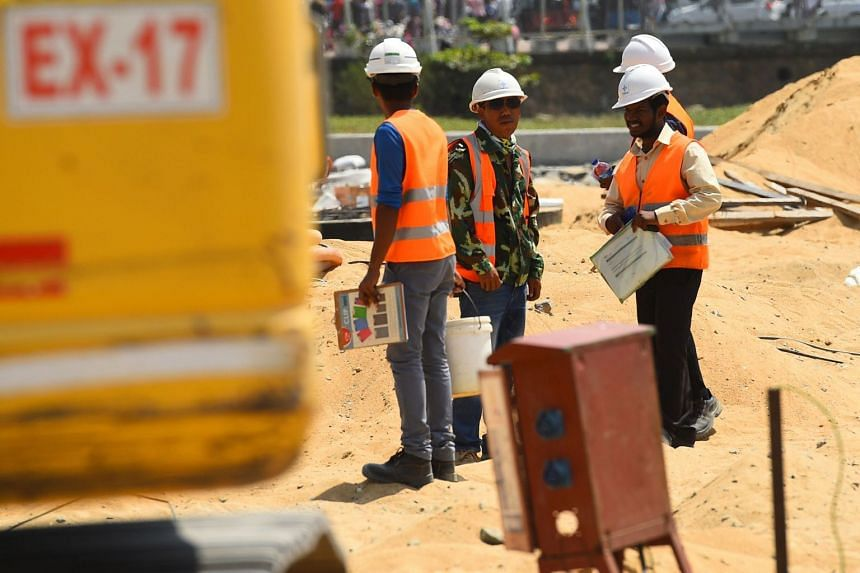 In a photo taken on Feb 24, 2020, Chinese and Sri Lankan labourers work at a construction site on reclaimed land, part of a Chinese-funded project for Port City, in Colombo.