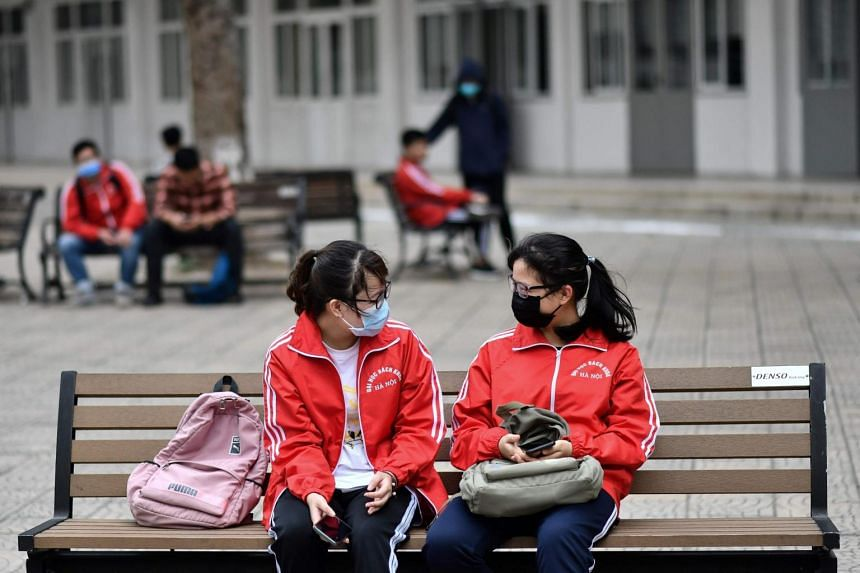 Students, wearing facemasks sit in a courtyard at the University of Science and Technology campus in Hanoi on March 2, 2020.