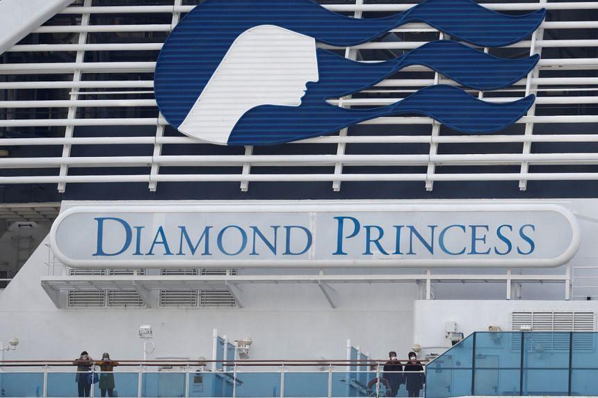 Masked passengers look on from on board the coronavirus-hit Diamond Princess cruise ship docked at Yokohama Port, south of Tokyo, Japan, on Feb 20, 2020.