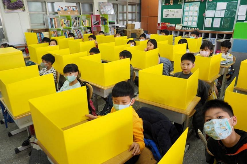Pupils, some wearing masks, sit behind partition boards as they attend classes at Dajia Elemental School in Taipei, Taiwan, on March 3, 2020. The school prepared the boards, made with PP Corrugated Board, to prevent infection of Covid-19 by saliva wh