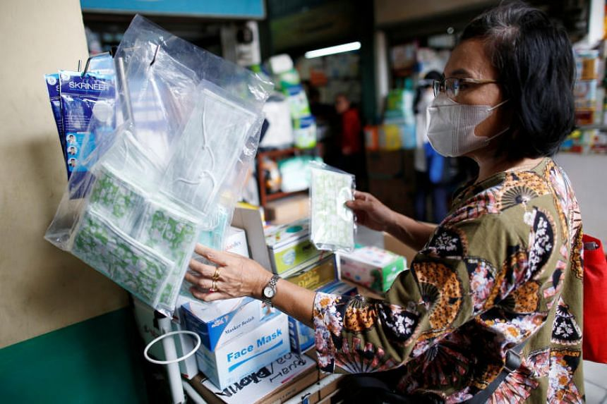 A woman shopping for surgical masks at a wholesale market for medical items in Jakarta  on Feb 13, 2020.