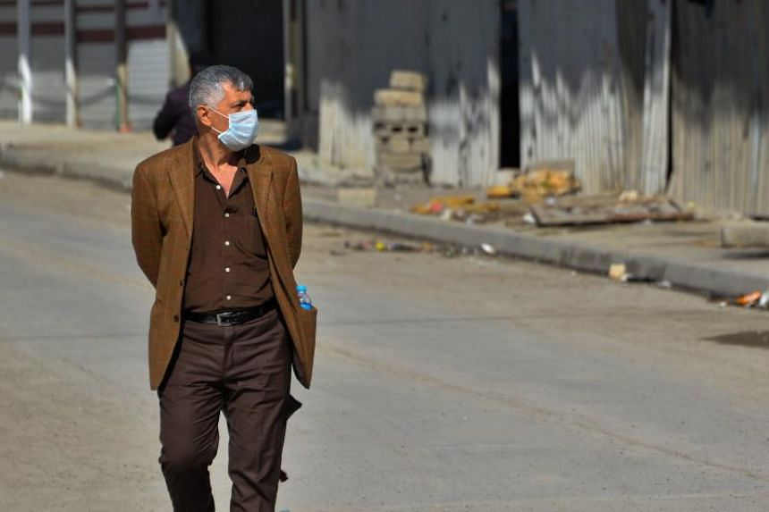 An Iraqi man wearing a protective mask walking in a deserted street in Iraq on March 3, 2020.