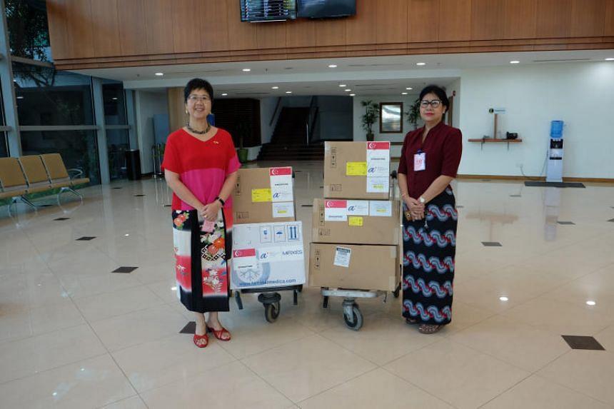 Singapore Ambassador to Myanmar Vanessa Chan (left) handing over Singapore's contributions to Myanmar National Health Laboratory director Htay Htay Tin.