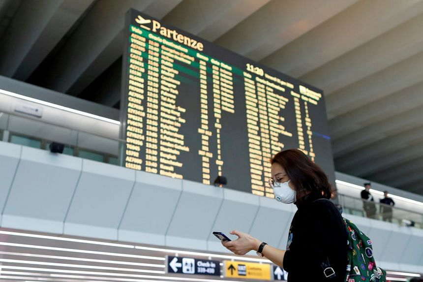 A passenger in a protective mask uses her phone at Rome's Fiumicino airport.