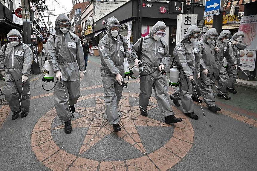 South Korean soldiers in protective gear spraying disinfectant in Seoul yesterday to help prevent the spread of the coronavirus. South Korea has the most cases of infections outside mainland China, weakening consumption and prompting the Bank of Kore