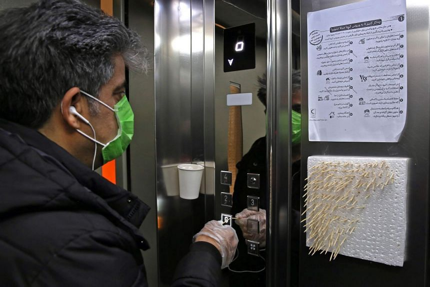 An Iranian man uses small sticks to push the elevator button at an office building in Teheran on March 4, 2020.