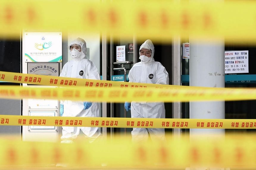 Medical staff wearing protective gear move are seen at a hospital in Daegu on March 1, 2020.
