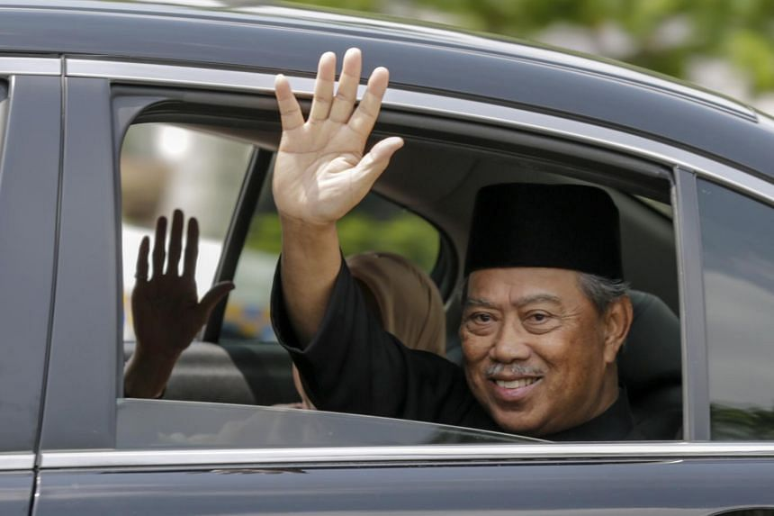 Malaysia's new Prime Minister Muhyiddin Yassin waves to media after his inauguration ceremony as the country's eighth prime minister, on March 1, 2020.