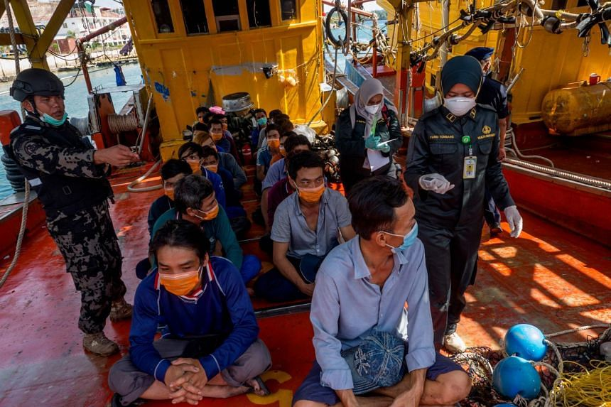 Indonesian officials with Vietnamese fishermen detained by the Indonesian authorities for illegal fishing in Batam on March 4, 2020.