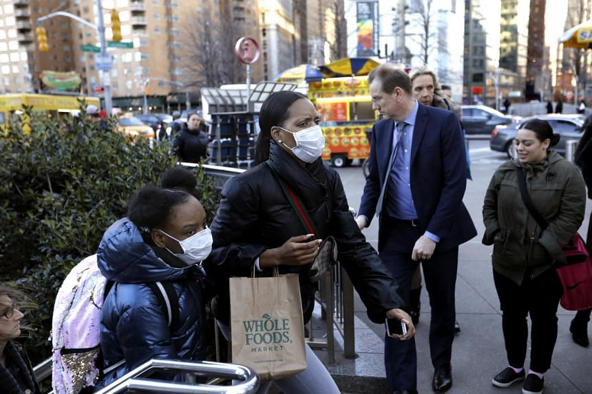 People emerge from the subway wearing face masks at Columbus Circle in New York, on March 4, 2020.