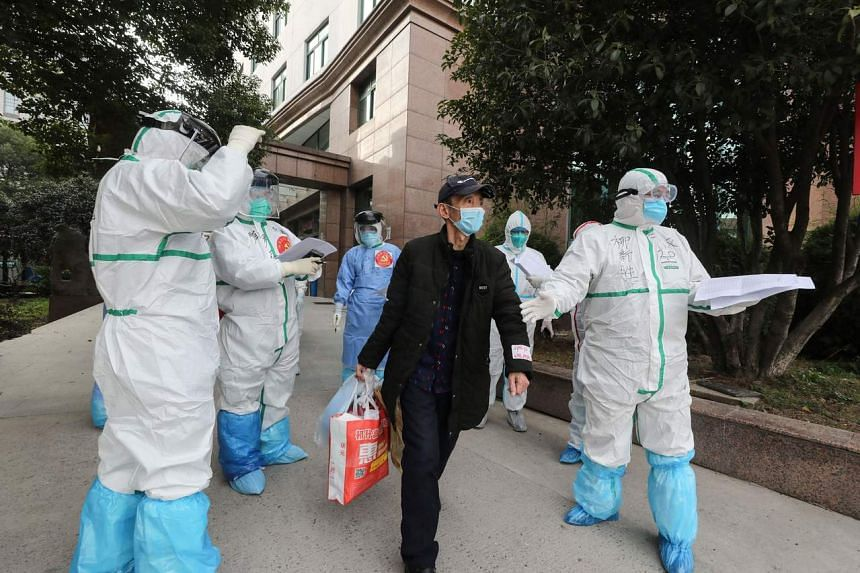 Medical staff assist a patient infected by the coronavirus leaving Wuhan No.3 Hospital to travel to Huoshenshan Hospital in Wuhan on March 4, 2020.