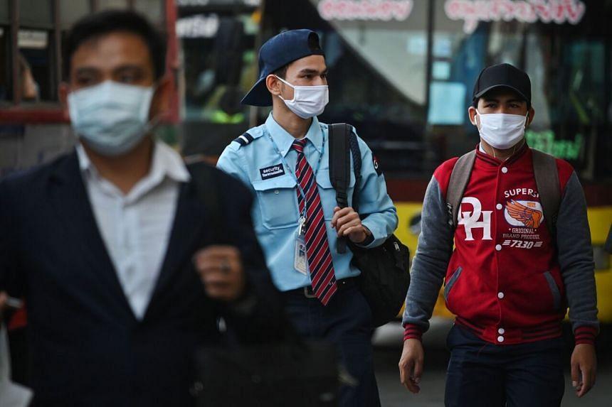Commuters, wearing masks walk in Bangkok on March 4, 2020.